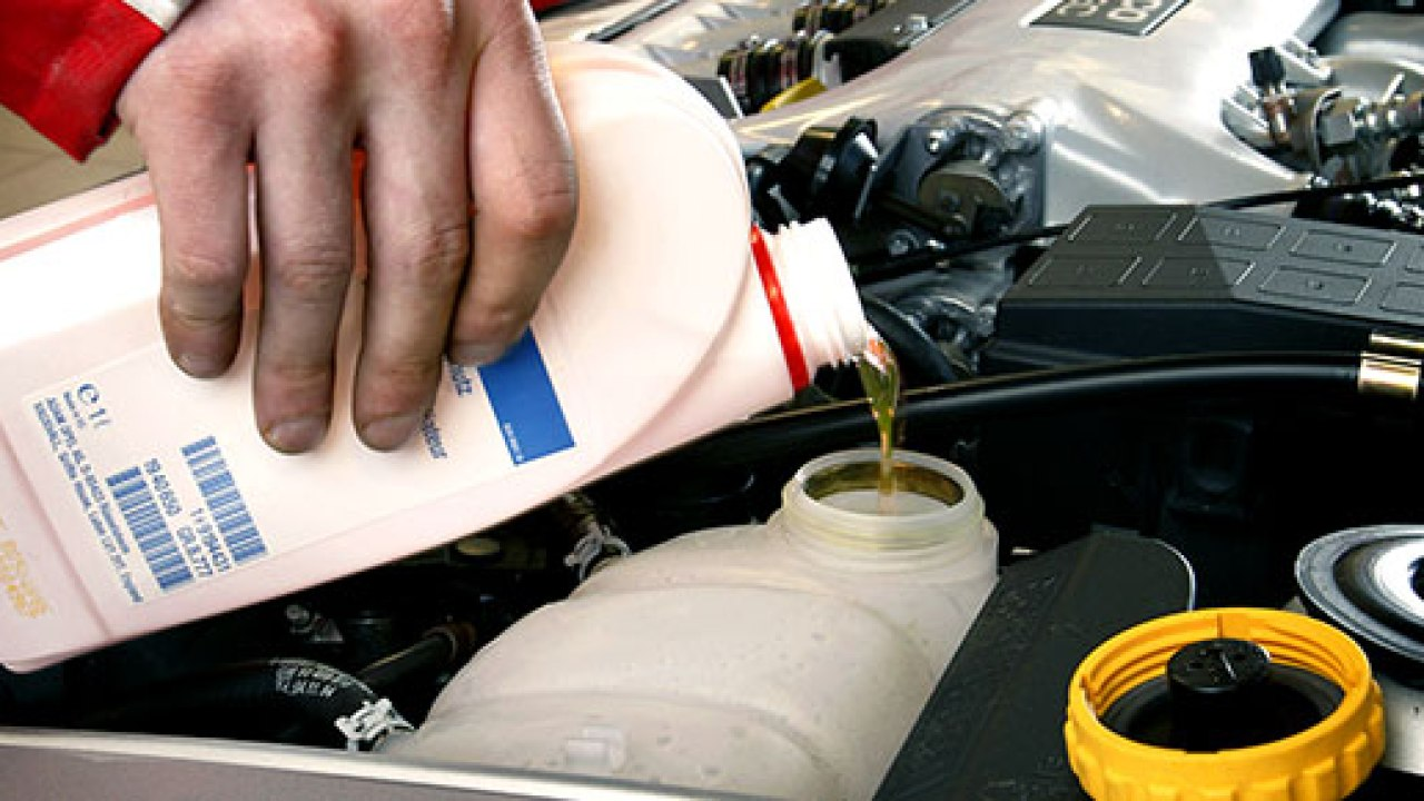 Man fillip up car engine with coolant