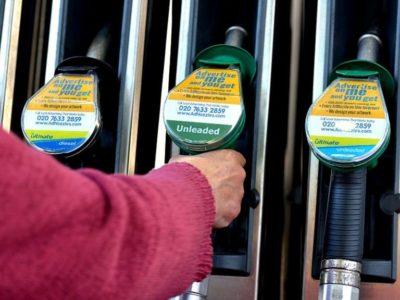 Woman selecting unleaded petrol at the pump